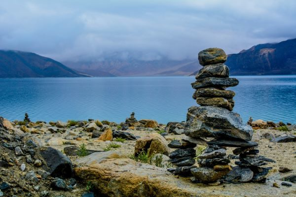 BlackRock Smaller Companies, pile of small rocks in front of a lake. Photo by Aaron Thomas on Unsplash