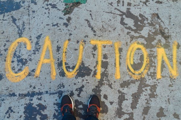 Personal Assets Trust, Caution written on a pavement, Photo by Goh Rhy Yan on Unsplash